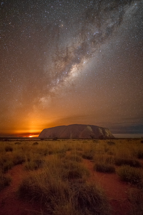 Milky Way rising over Uluru while a bushfire burns in the distance